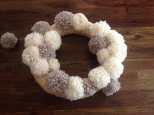 DIY Anthropologie inspired wreath. This wool pom pom wreath is perfect for th holidays. It's so beautiful-make it any color you want! Click here for a full tutorial.