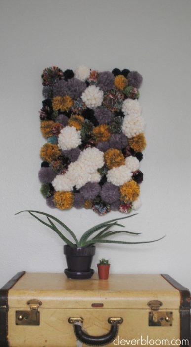Visit cleverbloom.com for easy to follow instructions on how to make this DIY Pom Pom Wall Hanging. It's super groovy with a 70's vibe that will make a great conversation piece!